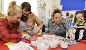 Mothers helping young children who have learning disabilities