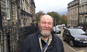 Man who has a learning disability smiling for the camera in Edinburgh