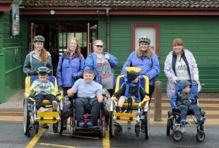 A group of wheelchair users and personal assistants heading outdoors