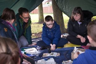 Children who have learning disabilities sitting in a tent learning about outdoors and nature