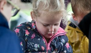 A young girl who has a learning disability attending an outdoor activity class and learning about nature