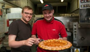 A man who has a learning disability, who works at Pizza Hut, being supported by his personal assistant to handle hot pizzas
