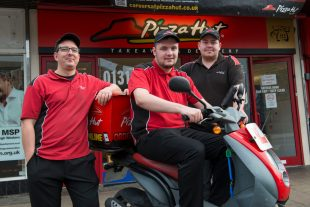 A man who has a learning disability posing with his colleagues outside Pizza Hut outlet