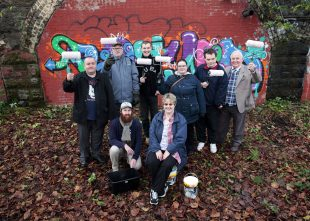 A group of people, some of them who have learning disabilities, posing for the camera holding paint brushes in front of a graffiti challenging hate crime