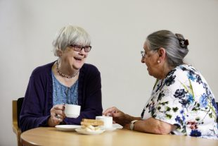 Two family carers having lunch and enjoying a chat