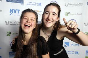 Two women laugh as they pose for the camera at a charity event