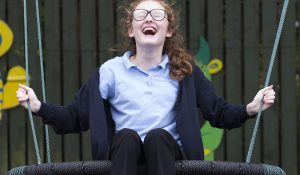 A girl who has a learning disability smiling while on a swing