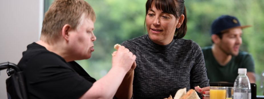 A woman supporting a man who has a learning disability to eat his sandwich