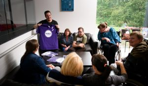 Fundraiser talking to a group of people who have learning disabilities while holding an ENABLE t-shirt