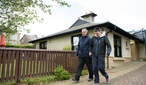 Man who has a learning disability leaving his house with his personal assistant