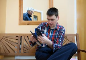 A man who has a learning disability reading a magazine in his own home with his personal assistant reflected in the mirror behind him