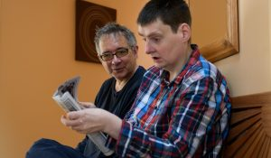 A man who has a learning disability reading a magazine in his own home with his personal assistant sitting next to him