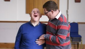 A man has his hand around the shoulders of a man who has Down's Syndrome, while he looks up and smiles
