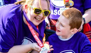 A woman holds charity walk medals as a boy smiles at her