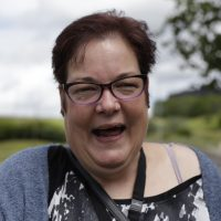 A woman who has a learning disability smiling for the camera