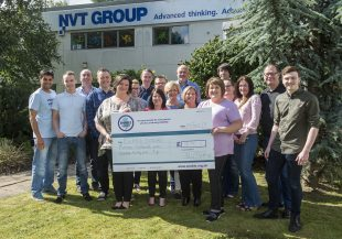 A group of staff posing with an oversized charity cheque