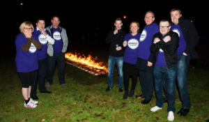 A group of men and women posing in front of an open fire before their firewalk challenge