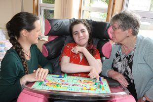 A woman who has a learning disability in her own home with two other women, playing monopoly on the tray attached to her wheelchair