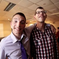 Two young men who have learning disability smiling at the camera in a pub