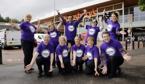 Staff from Sainsbury's wearing ENABLE shirts as they pose for camera outside their shop