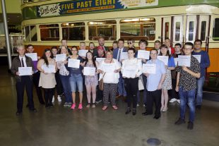 A group of people who have learning disabilities holding up their employment training certificates at the transport museum