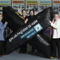 A groups of ACE members who have learning disabilities holding a big cross promoting election voting