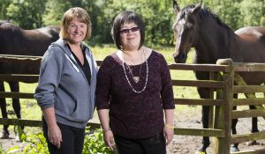 A woman who has a learning disability and her personal assistant smiling at the camera in front of horses