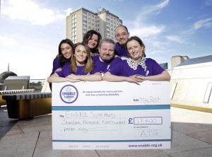 A group of people dressed in purple shirts posing behind an oversized cheque