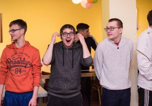 A group of young men who have learning disabilities standing up and smiling