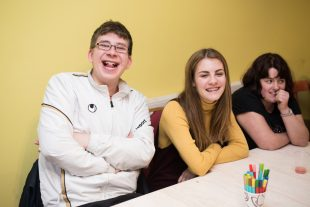 A group of people who have learning disabilities smiling at the camera