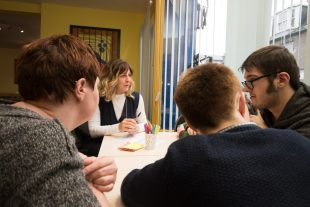 A group of people who have learning disabilities listening to their group facilitator