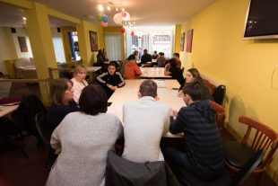 A group of people who have learning disabilities sitting around a table in a community hall