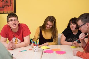 A group of young adults who have learning disabilities gathered around a table while one of them is writing on a post it note
