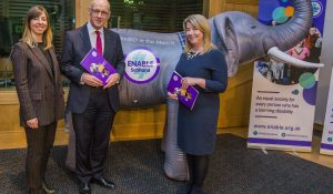 Two directors posing with Scottish minister in front of an inflatable elephant