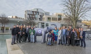 People who have learning disabilities and staff posting outside the Scottish Parliament with an inflatable elephant