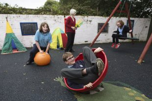 Schoolchildren who have a learning disability and personal assistant having fun in a playpark
