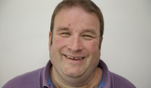 A close up photo of a man who has a learning disability smiling for the camera