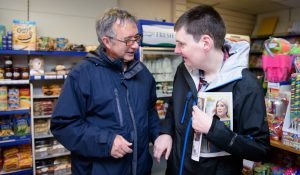 A man who has a learning disability being supported to go to his local cornershop