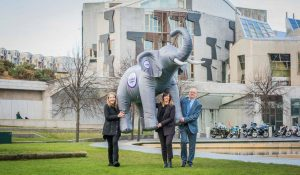A young woman who has learning disability, staff and a representative from the government holding an inflatable elephant outside Scottish Parliament