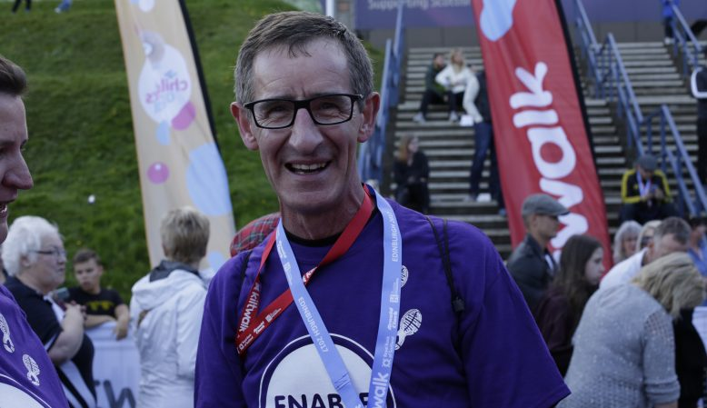 A man with medals around his neck smiling at the camera at the finish line of a charity event