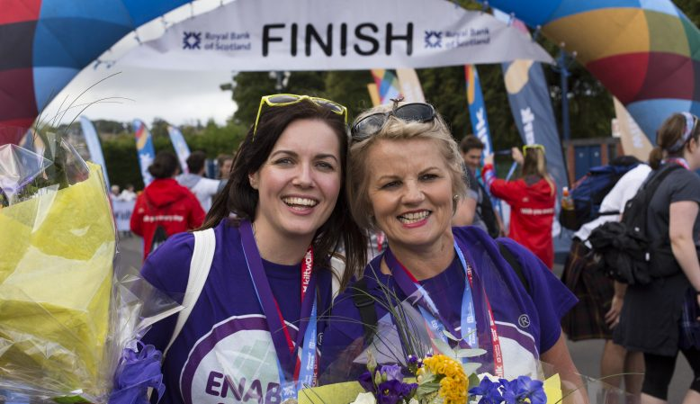 Two women with medals around their neck smiling at the camera at the finish line of a charity event