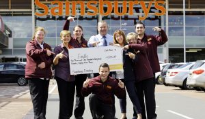 Staff from Sainsbury's holding an oversized cheque outside their shop