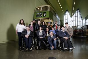 A group of people in front of an old bus at a charity campaign launch event