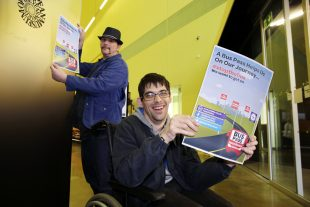 Two men who have learning disabilities posting for the camera while holding up charity campaign leaflets for #StoptheBus