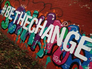 A photo of Be the Change graffiti on a red wall