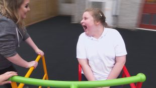 A girl who has a learning disability laughing as she is being pushed in a roundabout